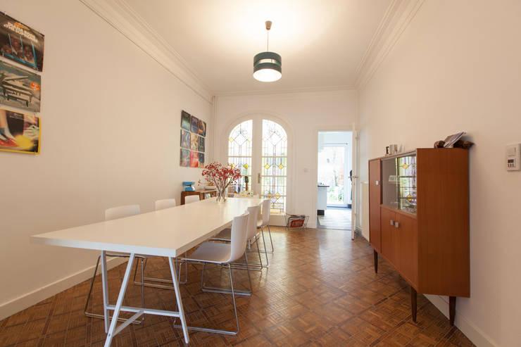 eetruimte met zicht op keuken en veranda: moderne Eetkamer door studio k