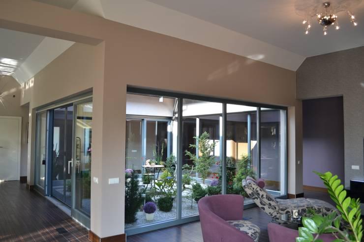 Dom z wewnętrznym PATIO: styl , w kategorii Okna zaprojektowany przez Autorskie Studio Projektu QUBATURA