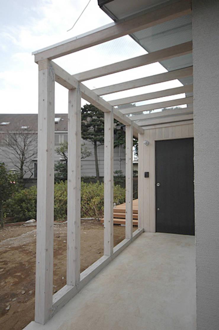 玄関前のガラス屋根のかかったアプローチ: 大庭建築設計事務所が手掛けた家です。