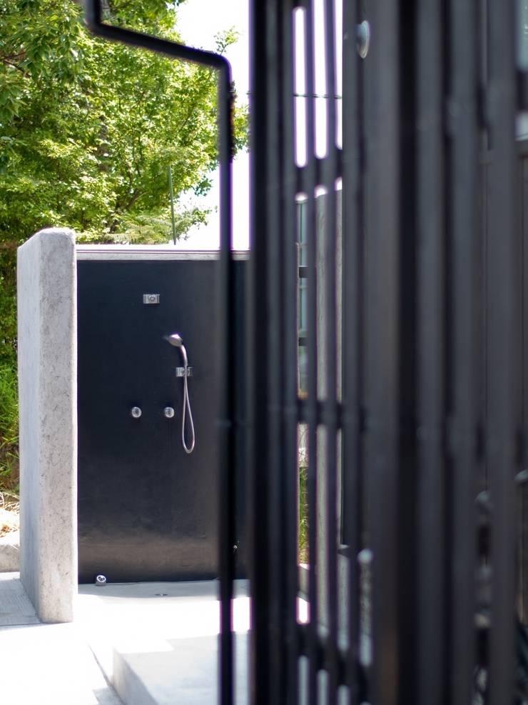 屋外シャワーコーナー: 篠田 望デザイン一級建築士事務所が手掛けた浴室です。