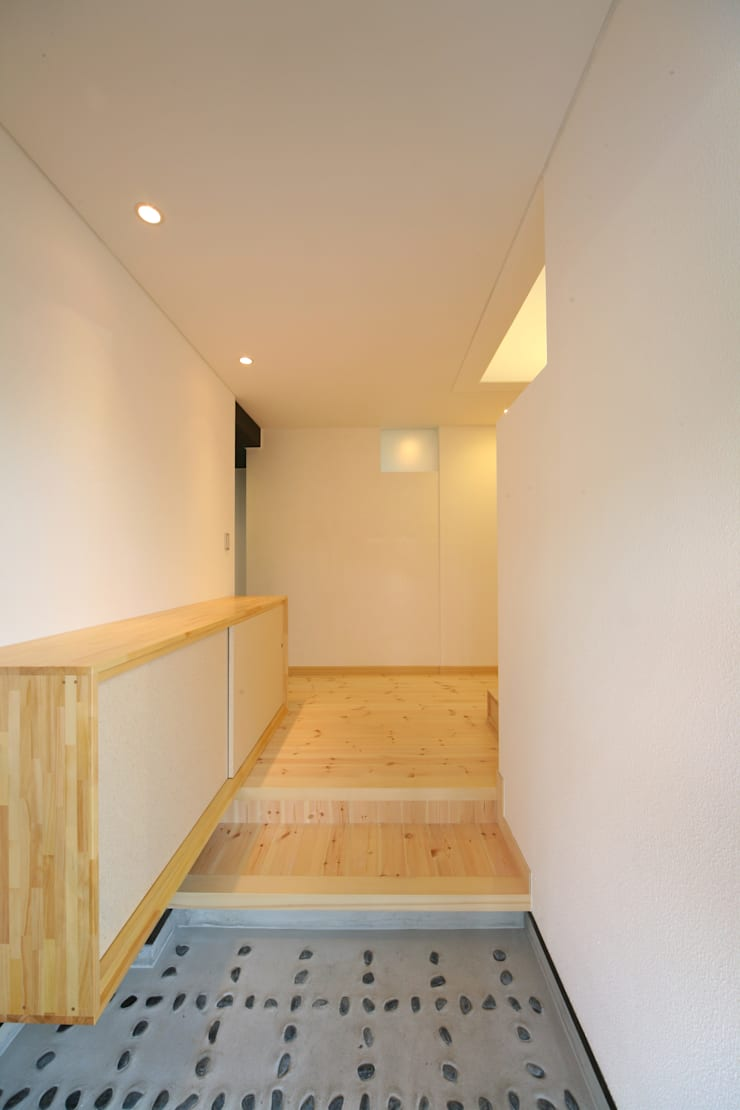 玄関ホール: 篠田 望デザイン一級建築士事務所が手掛けた壁です。