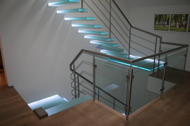 zwevende glazen trappen met wisselende verlichting van de zijkant gezien:  Gang, hal & trappenhuis door Allstairs Trappenshowroom