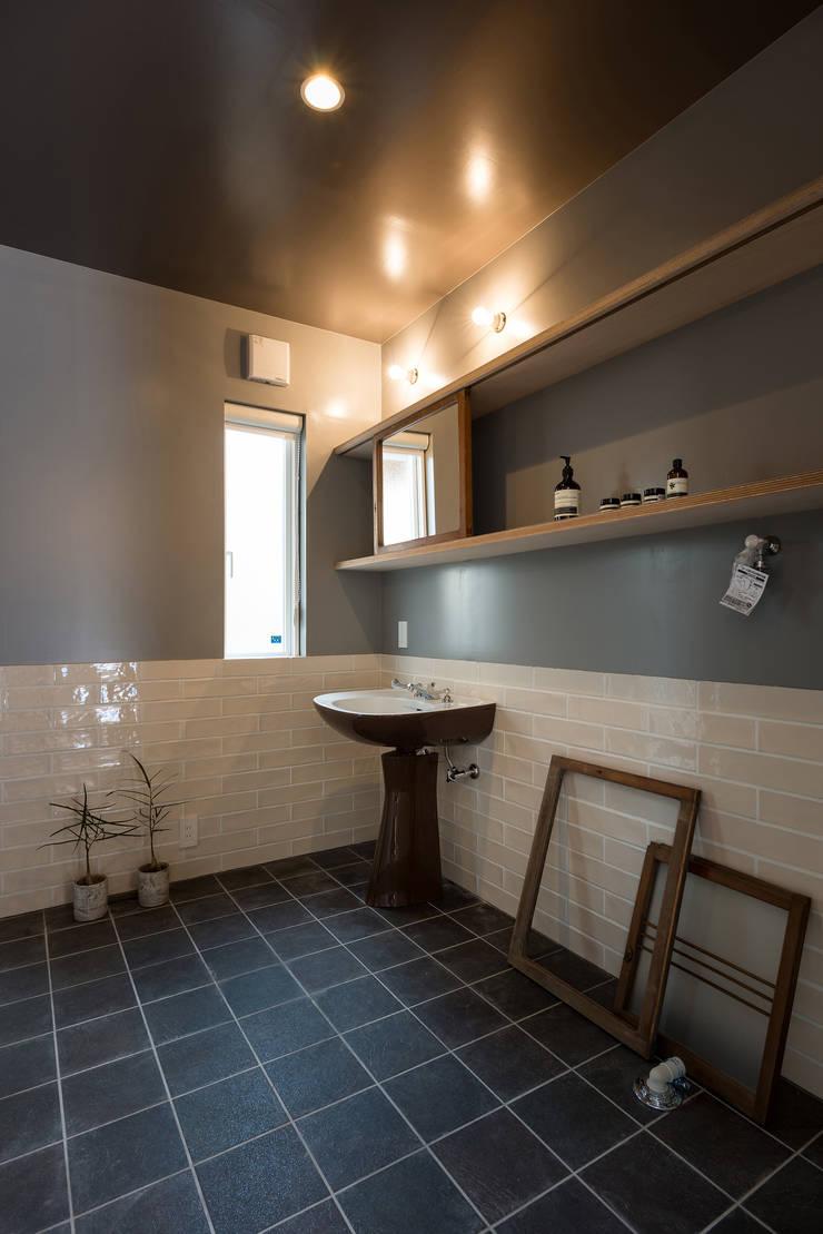 日本製のアンティーク洗面台と古い建具のミラー: エンジョイワークス一級建築士事務所が手掛けた浴室です。