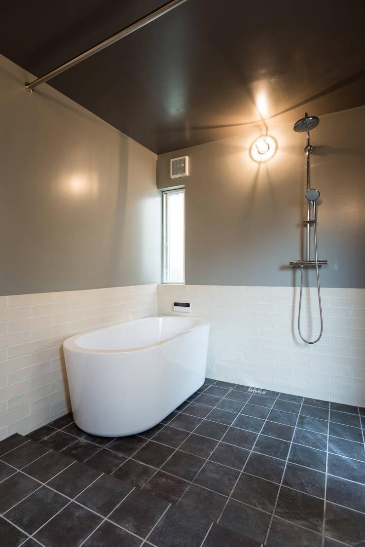 外から直行できるバスルーム: エンジョイワークス一級建築士事務所が手掛けた浴室です。