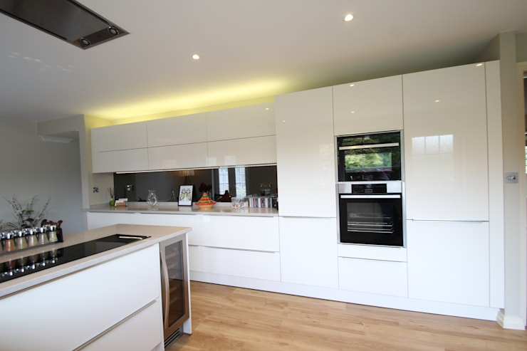 White gloss Schuller handled with Neff appliances and Ceaserstone worktops: modern Kitchen by AD3 Design Limited