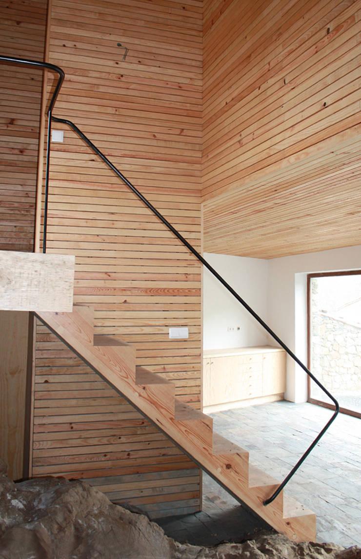 Vista da escada, cozinha e volume suspenso dos quartos: Corredores e halls de entrada  por Atelier do Corvo