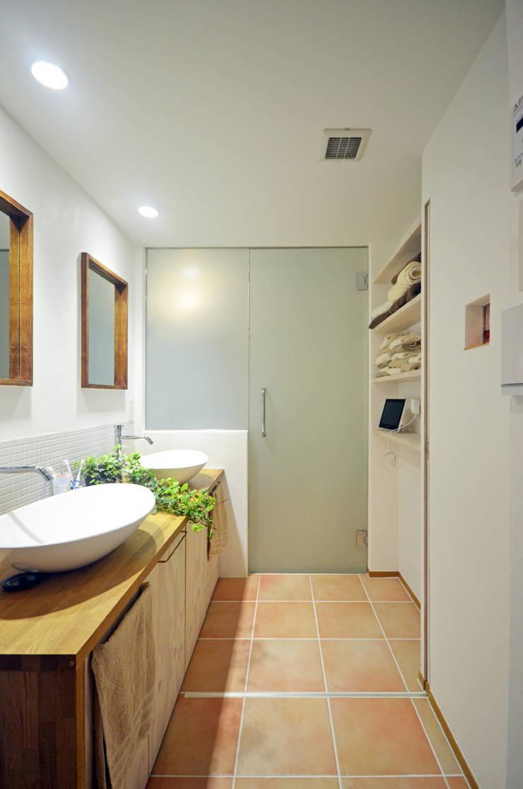 光が回る洗面所: 大塚高史建築設計事務所が手掛けた浴室です。