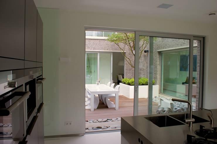 Eetterras dicht bij de keuken:  Terras door Stoop Tuinen, Modern