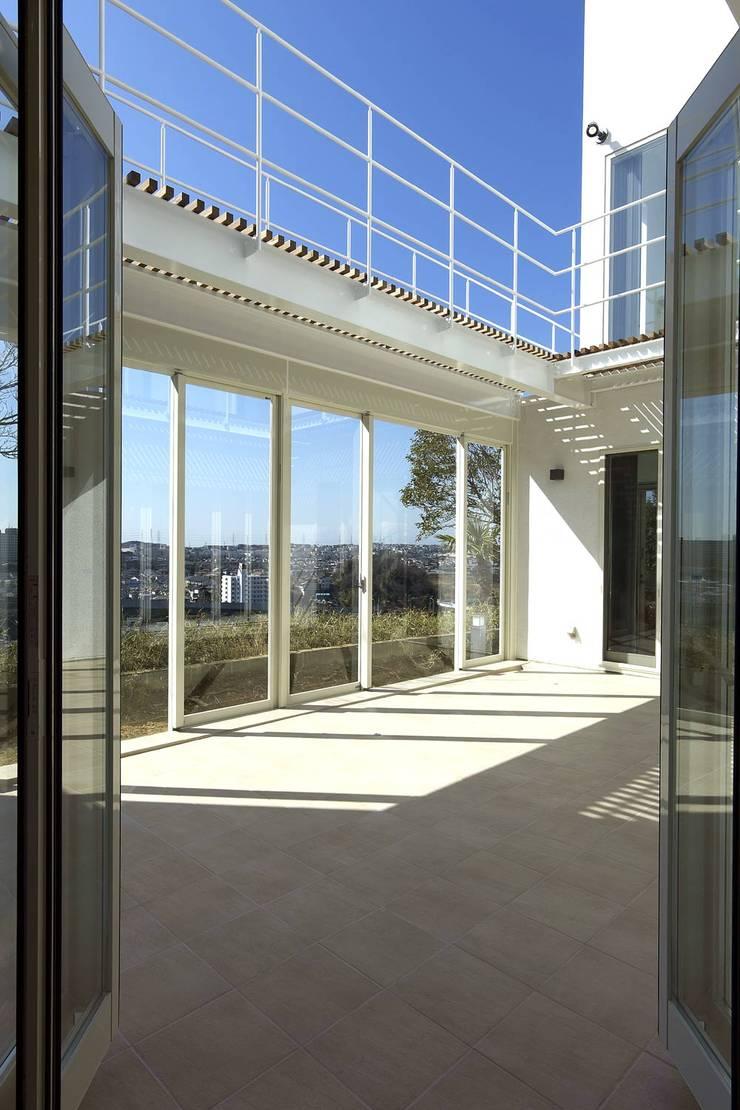 玄関からコート: (有)設計工房TOGAWAが手掛けたテラス・ベランダです。