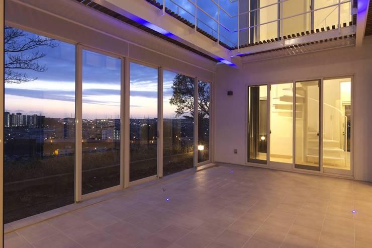 夕暮れのコート: (有)設計工房TOGAWAが手掛けたテラス・ベランダです。