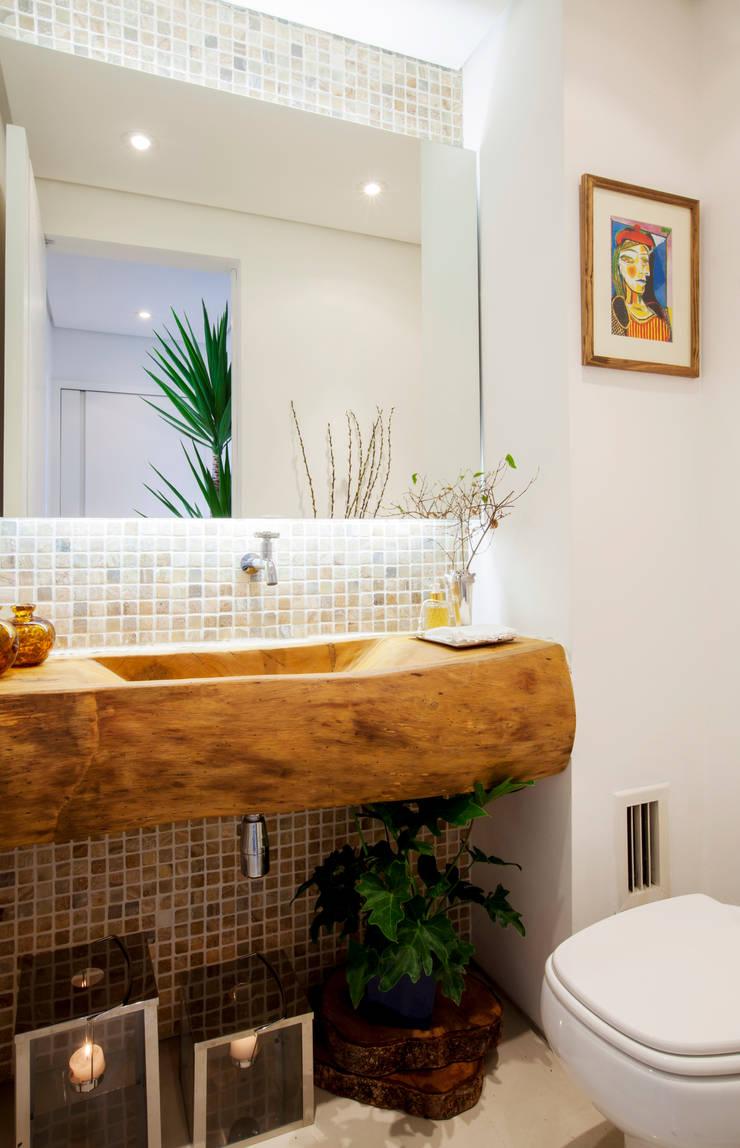 Lavabo com cuba esculpida em tora de madeira.: Banheiros  por Helô Marques Associados,