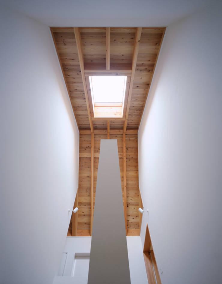 トップライトのある階段室: 久保田章敬建築研究所が手掛けた廊下 & 玄関です。,