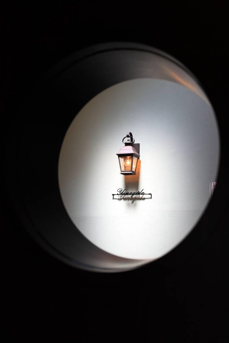 建具の小窓から階段室を覗く: 株式会社伏見屋一級建築士事務所が手掛けた廊下 & 玄関です。