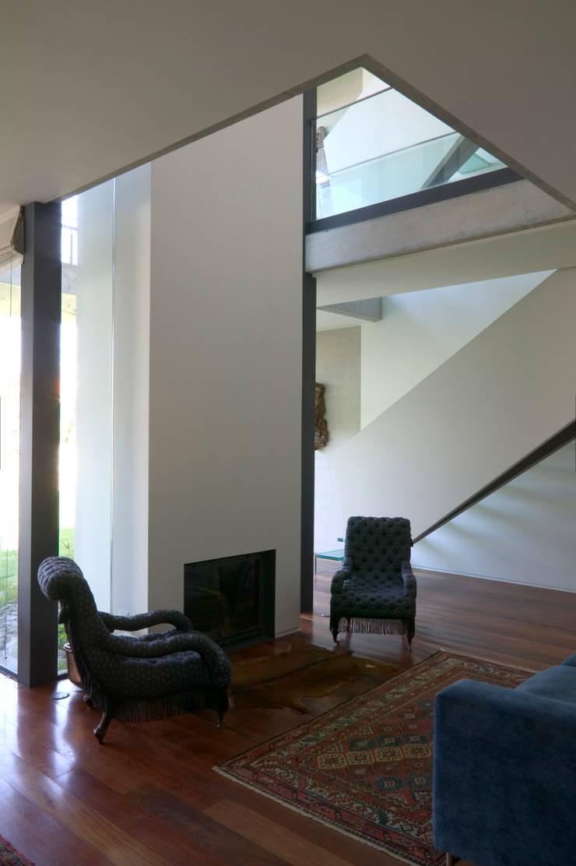 Casa III: Salas de estar  por A. BURMESTER ARQUITECTOS