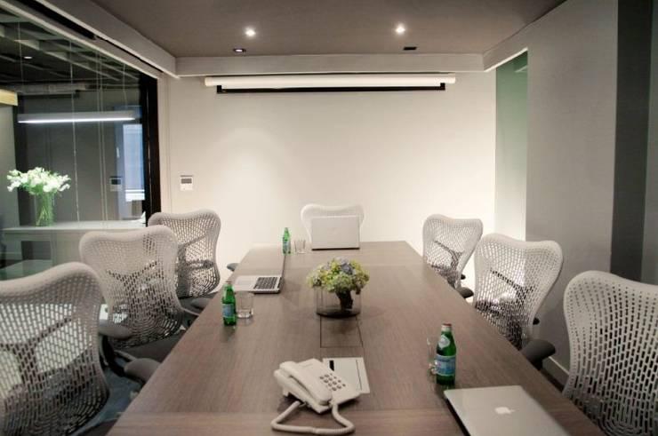 Sala de juntas. Mesa sobre diseño: Oficinas y tiendas de estilo  por Quinto Distrito Arquitectura