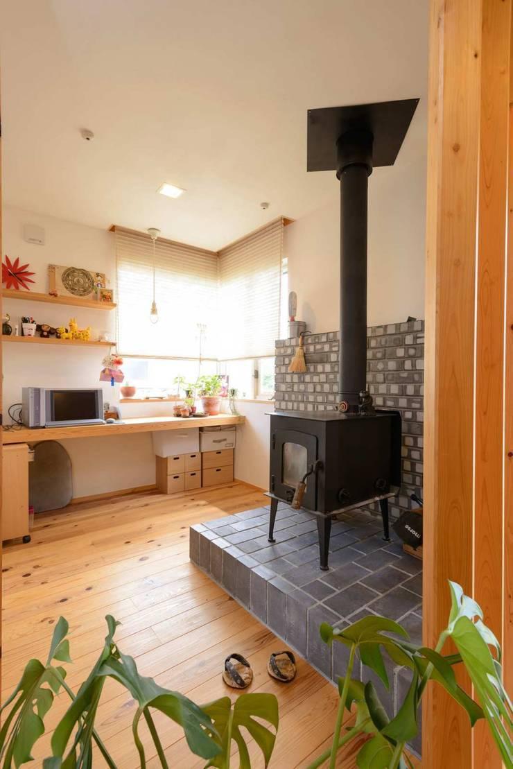 薪ストーブ: 建築アトリエTSUTSUMIが手掛けたリビングルームです。,