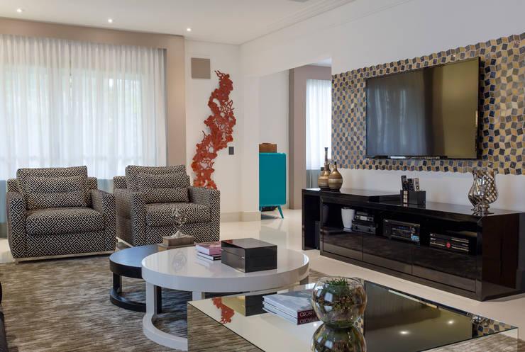 Detalhe escultura e TV: Salas de estar ecléticas por Helen Granzote Arquitetura e Interiores