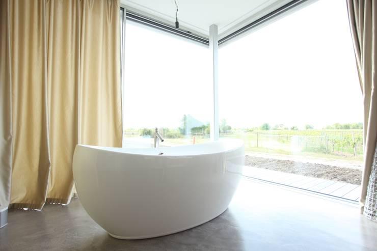 freistehende Badewanne mit Blick auf die Weinreben:  Badezimmer von Neugebauer Architekten BDA