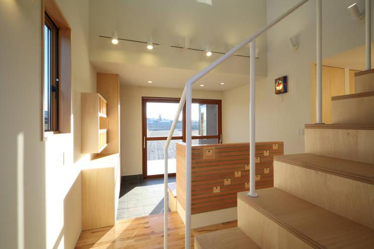 階段側より玄関土間を見る: office.neno1365が手掛けた廊下 & 玄関です。