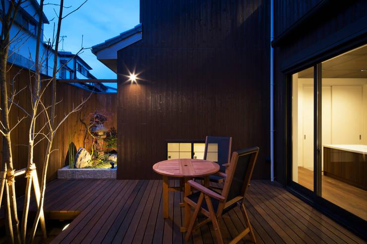 中庭夕景: 一級建築士事務所シンクスタジオが手掛けた庭です。