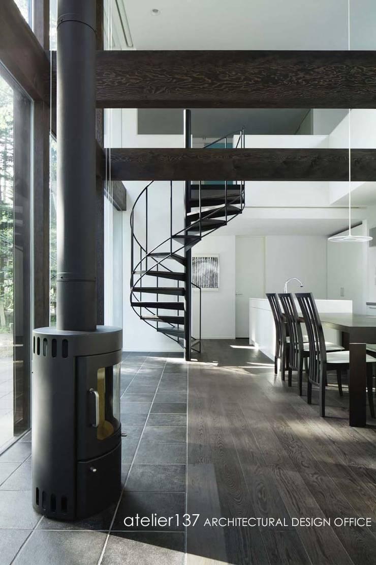 薪ストーブ+らせん階段: atelier137 ARCHITECTURAL DESIGN OFFICEが手掛けたリビングです。