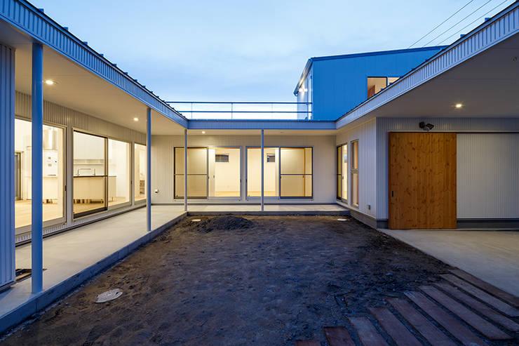 コの字の家 中庭夕景2: 腰越耕太建築設計事務所が手掛けた庭です。,