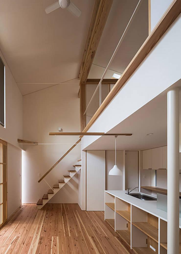 広間・吹抜と階段: 河合建築デザイン事務所が手掛けたリビングです。