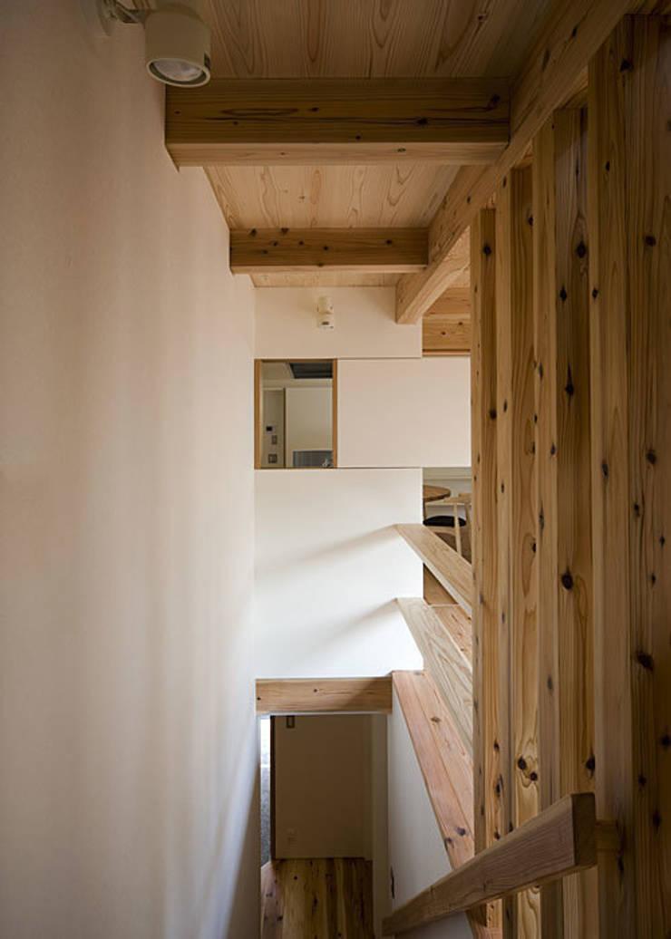 階段上部と台所小窓: 河合建築デザイン事務所が手掛けた廊下 & 玄関です。