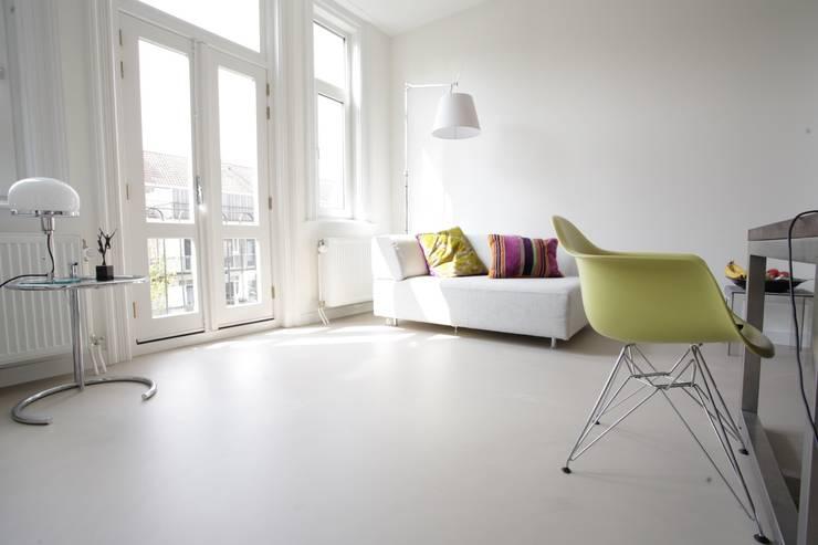 Grijze betonlook gietvloer in eetkamer:  Eetkamer door Motion Gietvloeren