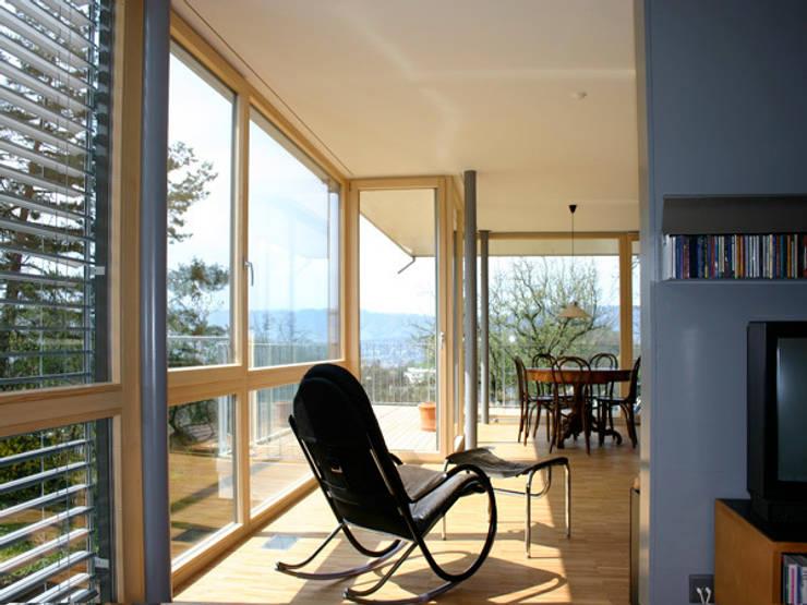 Blick längs durch Zimmerschicht: moderne Wohnzimmer von eidenbenz.architekt