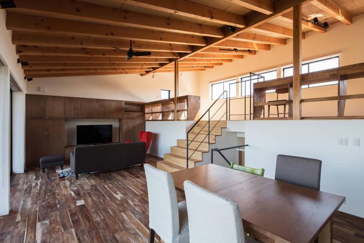 2階プレイルームと緩やかにつながる1.5階LDK: 一級建築士事務所シンクスタジオが手掛けたリビングです。