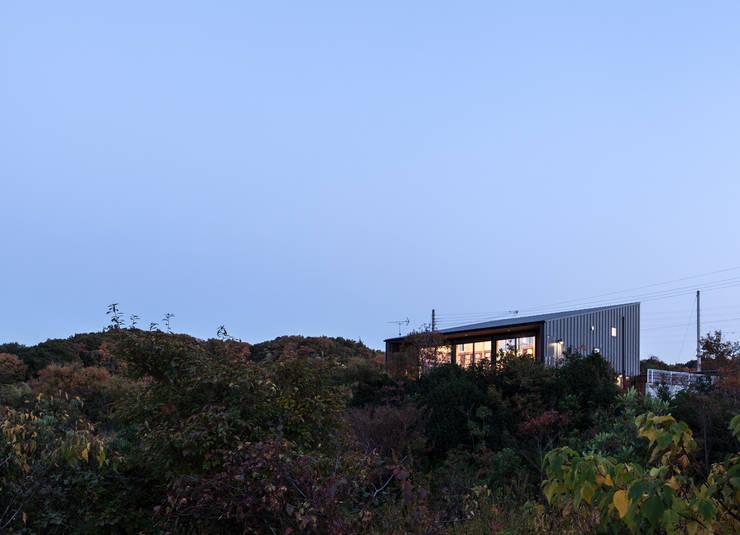 外観夕景: 一級建築士事務所シンクスタジオが手掛けた家です。