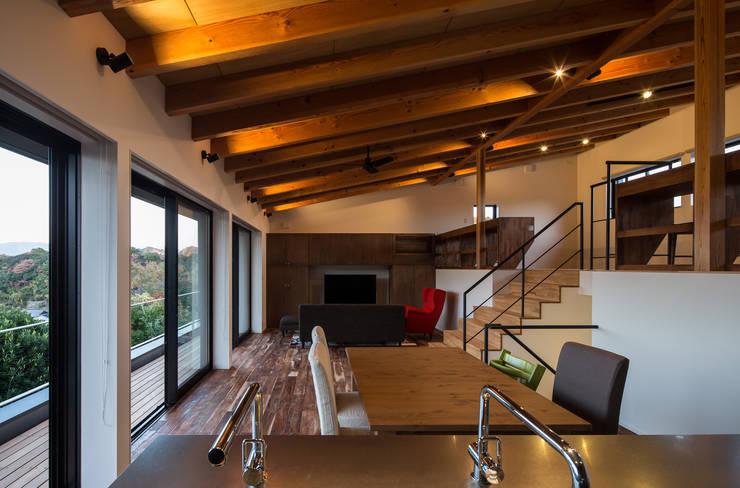 室内夕景: 一級建築士事務所シンクスタジオが手掛けたキッチンです。