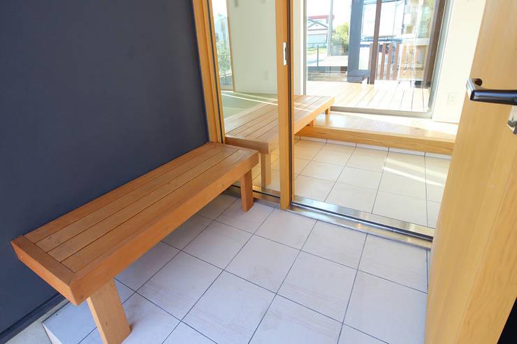 ベンチが内外を連続する玄関: シーズ・アーキスタディオ建築設計室が手掛けた廊下 & 玄関です。