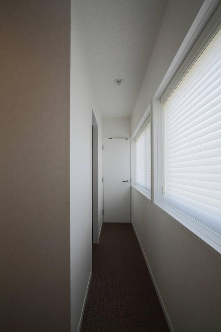 寝室から洗面室に通じる裏動線: 伊藤一郎建築設計事務所が手掛けた廊下 & 玄関です。
