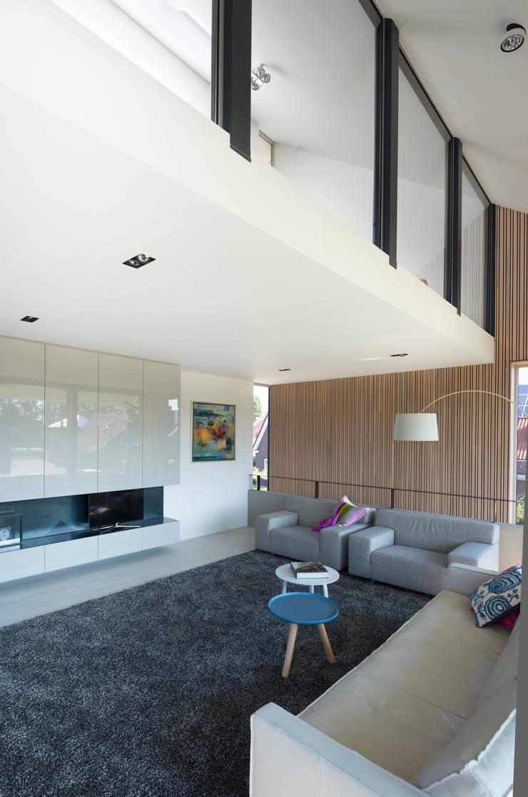 Woon- en werkkamer:  Woonkamer door Architect2GO
