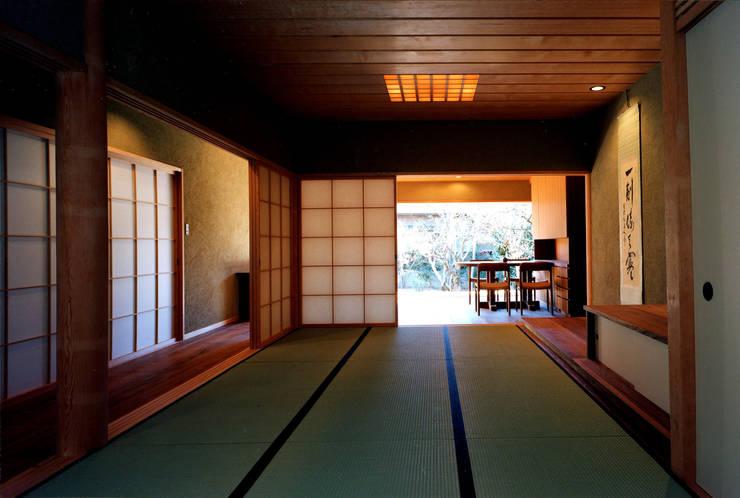 玄関から庭へ: 松井建築研究所が手掛けたリビングです。,