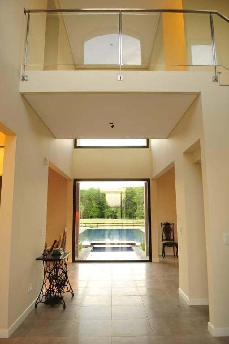 vista desde el hall en doble altura: Pasillos y recibidores de estilo  por Parrado Arquitectura,Moderno