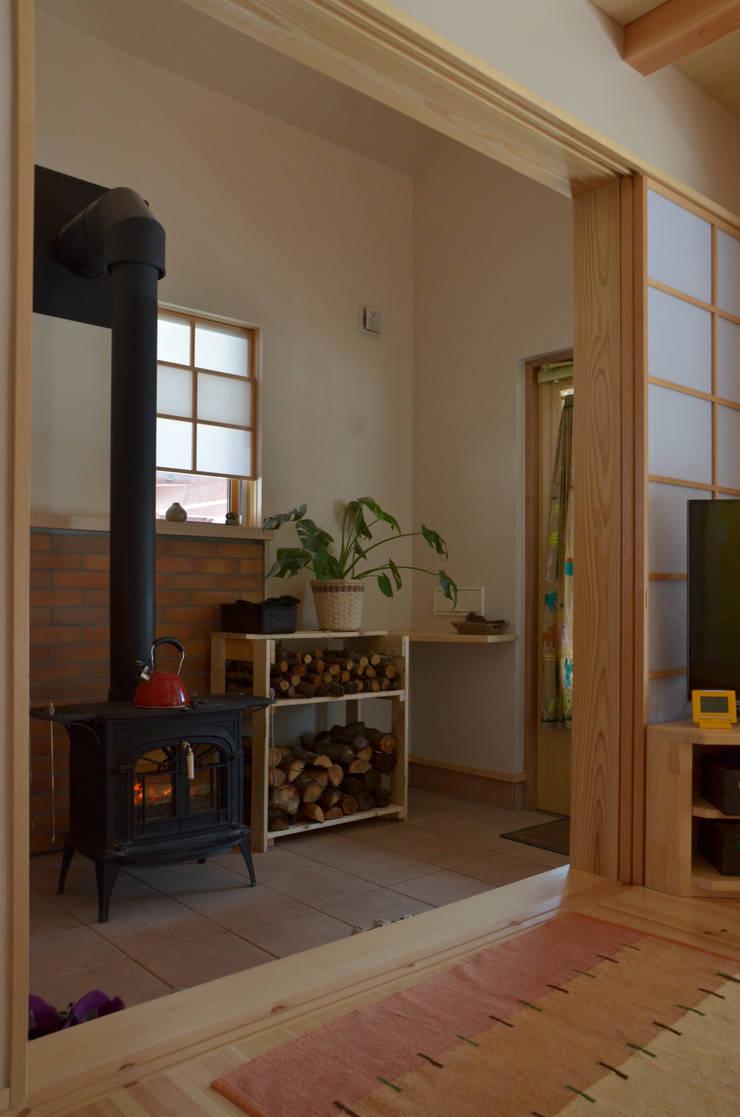 玄関土間にストーブ: (株)誠設計事務所が手掛けたです。