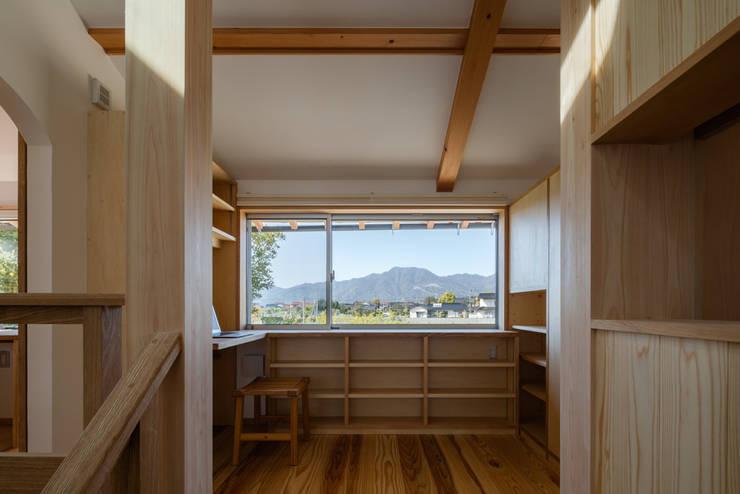 階段を上ると、北の窓から美しい山の稜線が見える: 小野育代建築設計事務所が手掛けた書斎です。
