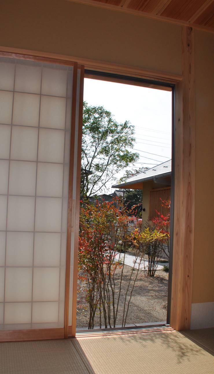 入側から前庭を見る・畳に映る南天の陰: 樹・中村昌平建築事務所が手掛けた枯山水です。