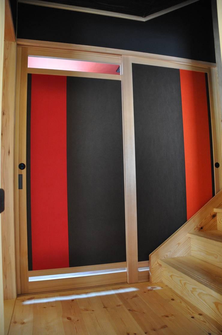 階階段ホール・ WC表側戸に紅と黒の帯を張る: 樹・中村昌平建築事務所が手掛けた玄関&廊下&階段です。
