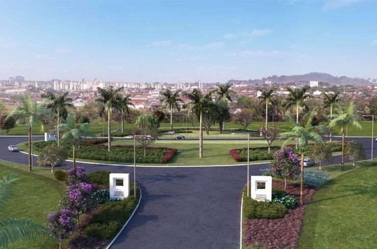 Entrada de condomínio marcada por palmeiras: Jardins tropicais por Roncato Paisagismo e Comércio de Plantas Ltda