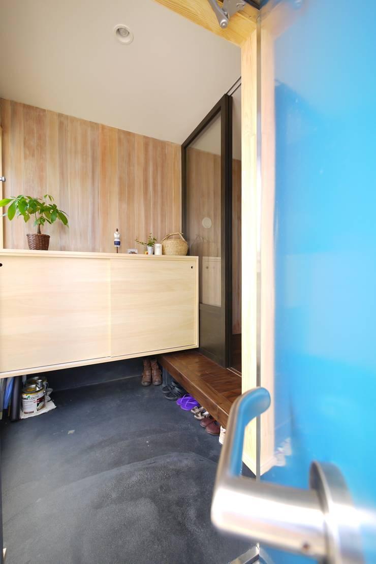ターコイズブルーのドアと玄関: 池田デザイン室(一級建築士事務所)が手掛けた窓です。