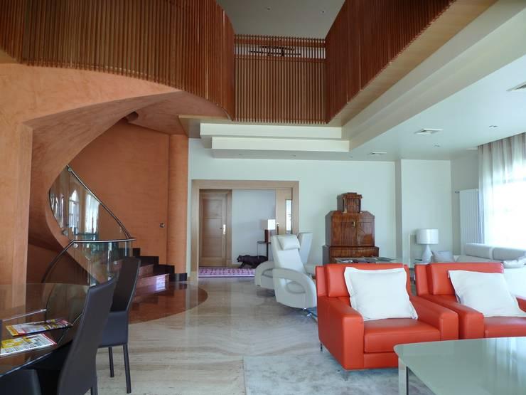 03-Casa Raúl. Sala con la escalera y doble altura. Marmol Travertino y Friso de madera maciza de cerezo: Salones de estilo  de DELSO ARQUITECTOS