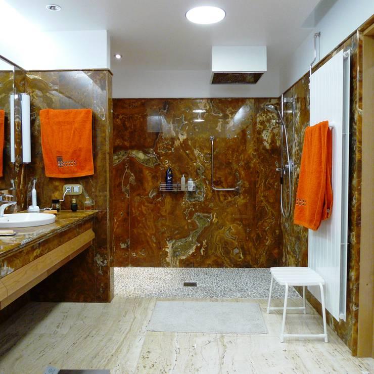 07-Casa Raúl-  Baño de uno de los dormitorios, acabado en Ónice Chocolate: Baños de estilo  de DELSO ARQUITECTOS