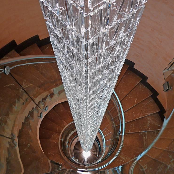 17-Casa Raúl-  Lampara colgada de teselas de vidrio veneciano (Fabbian) de 9 metros de altura. Dos encendidos azul y blanco: Vestíbulos, pasillos y escaleras de estilo  de DELSO ARQUITECTOS