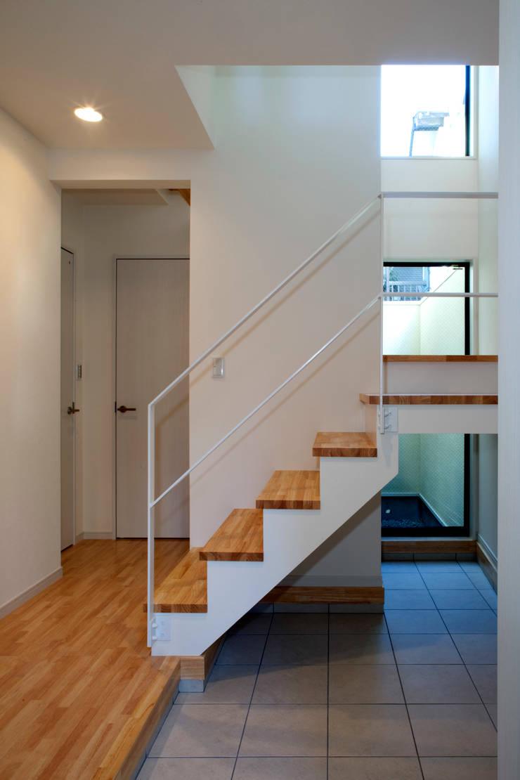 大島の家/エントランスホール階段: アトリエ・ノブリル一級建築士事務所が手掛けた廊下 & 玄関です。