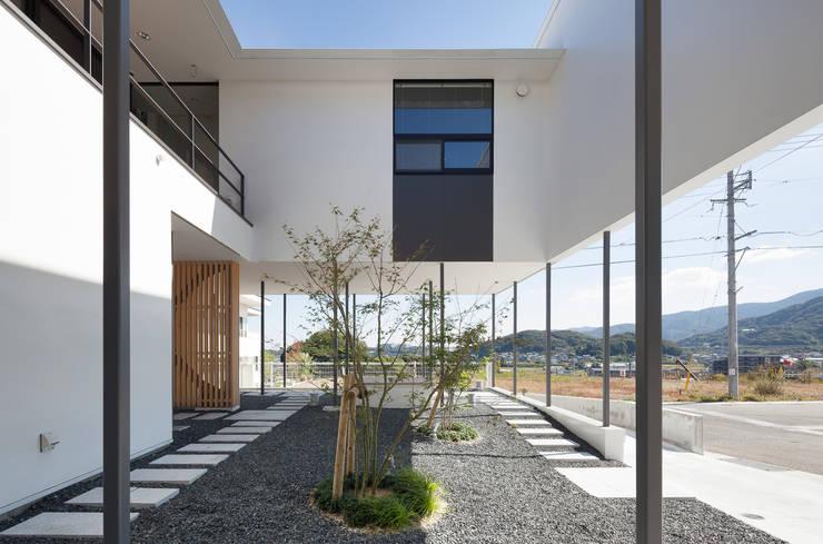 中庭にもなるピロティー: 松本匡弘建築設計事務所が手掛けたベランダです。