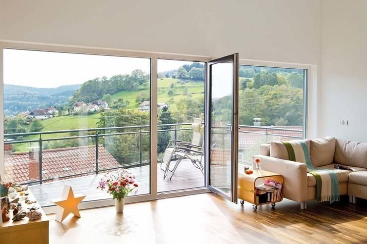 Frei geplantes Kundenhaus - Wohnzimmer mit direktem Zugang auf den Balkon: moderne Wohnzimmer von FingerHaus GmbH